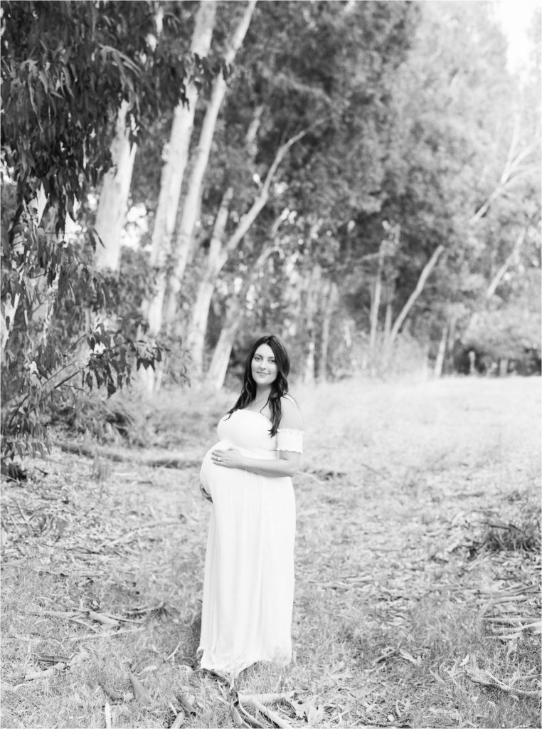 expecting mother in dress near trees